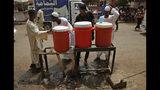 Sudanese drink water from a communal dispenser at a popular market, in Khartoum, Sudan, Monday, June 24, 2019. (AP Photo/Hussein Malla)