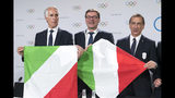 Italian National Olympic Committee (CONI) president Giovanni Malago, Italy's Under Secretary of State Giancarlo Giorgetti and the Mayor of Milan Giuseppe Sala, from left, hold flags during a press conference of the Milan-Cortina candidate cities the first day of the 134th Session of the International Olympic Committee (IOC), at the SwissTech Convention Centre, in Lausanne, Switzerland, Monday, June 24, 2019. The host city of the 2026 Olympic Winter Games will be decided during the134th IOC Session. Stockholm-Are in Sweden and Milan-Cortina in Italy are the two candidate cities for the Olympic Winter Games 2026. (Laurent Gillieron/Keystone via AP)