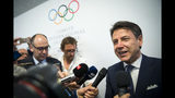 Italian Prime minister Giuseppe Conte speaks to journalists as he arrives during the first day of the 134th Session of the International Olympic Committee (IOC), at the SwissTech Convention Centre, in Lausanne, Switzerland, Monday, June 24, 2019. The host city of the 2026 Olympic Winter Games will be decided during the134th IOC Session. Stockholm-Are in Sweden and Milan-Cortina in Italy are the two candidate cities for the Olympic Winter Games 2026. (Jean-Christophe Bott/Keystone via AP)