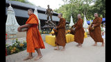 Thai Buddhist monks walk past the statue of Saman Gunan, the retired Thai SEAL diver who died during the rescue mission of a trapped soccer team, near the Tham Luang cave in Mae Sai, Chiang Rai province, Thailand Monday, June 24, 2019. The 12 boys and their coach attended a Buddhist merit-making ceremony at the Tham Luang to commemorate the one-year anniversary of their ordeal that saw them trapped in a flooded cave for more than two weeks. (AP Photo/Sakchai Lalit)