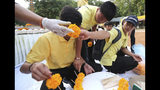 Members of the Wild Boars soccer team who were rescued from a flooded cave, prepare a flower for a religious ceremony near the Tham Luang cave in Mae Sai, Chiang Rai province, Thailand Monday, June 24, 2019. The 12 boys and their coach attended a Buddhist merit-making ceremony at the Tham Luang to commemorate the one-year anniversary of their ordeal that saw them trapped in a flooded cave for more than two weeks. (AP Photo/Sakchai Lalit)