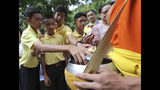 Members of the Wild Boars soccer team who were rescued from a flooded cave, offer foods to a Buddhist monk near the Tham Luang cave in Mae Sai, Chiang Rai province, Thailand Monday, June 24, 2019. The 12 boys and their coach attended a Buddhist merit-making ceremony at the Tham Luang to commemorate the one-year anniversary of their ordeal that saw them trapped in a flooded cave for more than two weeks. (AP Photo/Sakchai Lalit)