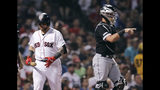 Boston Red Sox's Christian Vazquez, left, heads back to the dugout after striking out with the bases loaded, as Chicago White Sox catcher James McCann points to pitcher Lucas Giolito during the sixth inning of a baseball game at Fenway Park in Boston, Monday, June 24, 2019. (AP Photo/Charles Krupa)
