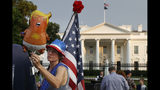 """FILE - In this May 18, 2019 file photo, a woman who described herself only as """"a resister"""" adjusts a """"Trump baby"""" balloon at the start of a protest against President Donald Trump along Pennsylvania Ave., outside the White House in Washington. President Trump is being trolled by an angry diaper-clad caricature armed with a cell phone. It's Baby Trump, the blimp that has become synonymous with resistance to the American president. The balloon has been cloned multiples times over and become something of a celebrity _ for at least one slice of the U.S. electorate. He's also emerged as a rallying point for supporters of the president who see the blimp as evidence of just how over-the-top the opposition has become. (AP Photo/Jacquelyn Martin)"""