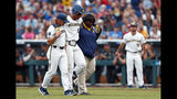 Michigan designated hitter Jordan Nwogu (42) is helped of the field after being injured trying to reach first base against Vanderbilt in the third inning of Game 2 of the NCAA College World Series baseball finals in Omaha, Neb., Tuesday, June 25, 2019. (AP Photo/John Peterson)