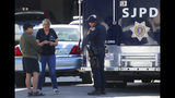 Members of the San Jose Police Department talk with an unidentified man, left, near the scene where five people were killed Monday, June 24, 2019, in San Jose, Calif. A gunman shot and killed four people then turned the gun on himself after an hours-long standoff with police in California, authorities said Monday. San Jose police saw several family members fleeing a home when police responded to multiple calls of shots fired Sunday night. (Aric Crabb/Bay Area News Group via AP)