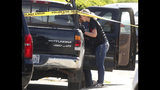 A forensic analyst with the San Jose Police Department searches a truck near scene where five people were killed Monday, June 24, 2019, in San Jose, Calif. A gunman shot and killed four people then turned the gun on himself after an hours-long standoff with police in California, authorities said Monday. San Jose police saw several family members fleeing a home when police responded to multiple calls of shots fired Sunday night. (Aric Crabb/Bay Area News Group via AP)