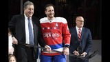 """FILE - In this Jan. 18, 2019, file photo, Washington Capitals defenseman Brooks Orpik, center, poses with Dick Patrick, left, team president, and Bill Daly, deputy NHL commissioner, after he was given a silver stick during a ceremony to honor Opik for playing 1,000 NHL hockey games, before the team's matchup against the New York Islanders in Washington. Orpik has decided to retire after 15 seasons and two Stanley Cup championships. The 38-year-old announced his retirement Tuesday, June 25, 2019. Orpik says his body is """"telling me it is time to move on to something new"""" after 1,171 NHL regular-season and playoff games. (AP Photo/Nick Wass, File)"""