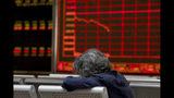 A woman rests as she monitors stock prices at a brokerage in Beijing on Tuesday, June 25, 2019. Major Asian stock markets declined Tuesday as traders looked ahead to a meeting between the American and Chinese presidents amid hopes for renewed trade talks. (AP Photo/Ng Han Guan)
