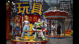 "A woman browses her photo after taking with her friend near the American latest animated film ""Toy Story 4"" promotion decoration on display at the capital city's popular shopping mall in Beijing, Tuesday, June 25, 2019. China says its trade negotiators are talking to their U.S. counterparts on how to resolve disputes ahead of an expected meeting between their two heads of state at the G20 meeting in Japan later this week. (AP Photo/Andy Wong)"