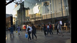 In this Saturday June 15, 2019 photo pedestrians walk past an Apple store along the 3rd Street Promenade in Santa Monica, Calif. On Tuesday, June 25, the Conference Board releases its June index on U.S. consumer confidence. (AP Photo/Richard Vogel)