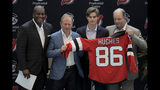 New Jersey Devils forward Jack Hughes, center right, the No. 1 overall pick in the 2019 NHL draft, poses for photographers with former NHL player Kevin Weekes, far left, Josh Harris, second from left, managing partner of Harris Blitzer Sports & Entertainment, and Ray Shero, Devils executive vice president and general manager, during a news conference introducing the prospect to local media, Tuesday, June 25, 2019, in Newark, N.J. (AP Photo/Julio Cortez)