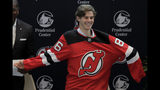 New Jersey Devils forward Jack Hughes, the No. 1 overall pick in the 2019 NHL draft, puts on a jersey during a news conference introducing the prospect to local media, Tuesday, June 25, 2019, in Newark, N.J. (AP Photo/Julio Cortez)
