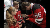 New Jersey Devils forward Jack Hughes, right, the No. 1 overall pick in the 2019 NHL hockey draft, signs autographs for Nicholas Palumbo, 12, center, and his sister Grace Palumbo, 10, from Nutley, N.J., after a news conference introducing the prospect to local media, Tuesday, June 25, 2019, in Newark, N.J. After getting the autograph, Nicholas Palumbo headed out to partake in his sixth grade graduation from Spring Garden Elementary School. (AP Photo/Julio Cortez)