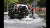 FILE- In this Sept. 30, 2015 file photo, a woman gets a ride on a police truck navigating a flooded street in Miami Beach, Fla. The street flooding was in part caused by high tides due to the lunar cycle, according to the National Weather Service. When Democratic presidential candidates meet in Miami for their first debate it'll be in what you could call the country's Ground Zero for any climate-related sea level rise. (AP Photo/Lynne Sladky, File)