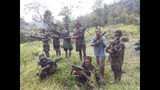 In this photo taken in May 2019, and released by the West Papua Liberation Army-Free Papua Organization, men and boys from the West Papua Liberation Army pose with weapons in the Nduga region of the central highlands, Papua province, Indonesia. (West Papua Liberation Army-Free Papua Organization via AP)