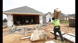 In this June 19, 2019, photo a worker carries supplies for a new house in a Brandon, Miss., neighborhood. On Tuesday, June 25, The Commerce Department reports on sales of new homes in May. (AP Photo/Rogelio V. Solis)