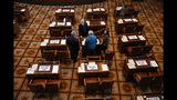 FILE - In this May 7, 2019, file photo, a group including three Democratic senators stand among the empty desks of Republican senators during a Senate floor session at the Oregon State Capitol in Salem, Ore. The divide in Oregon between the state's liberal urban centers and its conservative rural areas makes it ripe for the political crisis unfolding over sweeping climate legislation. Eleven Republican senators are entering the seventh day of a walkout to deny the supermajority Democrats the quorum needed to vote on a cap-and-trade bill that would be the second of its kind in the U.S. (Connor Radnovich/Statesman-Journal via AP, File)
