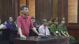 "Michael Nguyen stands during his trial, Monday, June 24, 2019, in Ho Chin Minh City, Vietnam. The American of Vietnamese origin was sentenced to 12 years in prison for ""attempt to overthrow the state."" (Nguyen Thanh Chung/Vietnam News Agency via AP)"