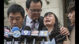 Lifeng Ye, the mother of slain University of Illinois scholar Yingying Zhang, cries out in grief as her husband Ronggao Zhang, far left, addresses the media after a jury found Brendt Christensen guilty of her murder Monday, June 24, 2019 outside the U.S. Federal Courthouse in Peoria, Ill. Consoling her is her son Zhengyang Zhang, far right, and family friend Dr. Kim Tee. (Matt Dayhoff/Journal Star via AP)