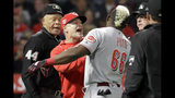 Cincinnati Reds' Yasiel Puig, right, is held back by manager David Bell after the pair were ejected by home plate umpire Kerwin Danley, left, during the sixth inning of the team's baseball game against the Los Angeles Angels in Anaheim, Calif., Tuesday, June 25, 2019. (AP Photo/Chris Carlson)