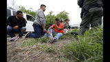 FILE - In this March 14, 2019, file photo, a Border Patrol agent talks with a group suspected of having entered the U.S. illegally near McAllen, Texas. Hundreds of thousands of people have been arriving at the border in recent months, many of them families fleeing violence and poverty in Central America. Once they reach the border, they can take different paths to try to get into the U.S. . (AP Photo/Eric Gay, File)