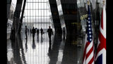 People walk in the main arrival space prior to a meeting of NATO defense ministers at NATO headquarters in Brussels, Wednesday, June 26, 2019. (AP Photo/Virginia Mayo, Pool)