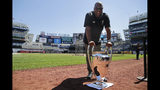 Former Liverpool FC player John Barnes poses for a picture with a replica of the Champions League trophy before a baseball game at Yankee Stadium, Wednesday, June 26, 2019, in New York. Liverpool FC will face Sporting Club of Portugal in a friendly match at Yankee Stadium on July 24, 2019. (AP Photo/Seth Wenig)