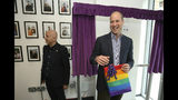 Britain's Prince William, the Duke of Cambridge, reacts to receiving a gift bag from trust chief executive officer Tim Sigsworth, during a visit to the Albert Kennedy Trust to learn about the issue of LGBTQ youth homelessness and the unique approach that the organisation is taking to tackling the problem, in London, Wednesday, June 26, 2019. (Jonathan Brady/Pool Photo via AP)