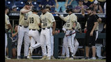 Vanderbilt's Pat DeMarco (18) is congratulated by teammates after scoring a run against Michigan during the seventh inning of Game 3 of the NCAA College World Series baseball finals in Omaha, Neb., Wednesday, June 26, 2019. (AP Photo/Nati Harnik)
