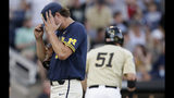 Michigan pitcher Jeff Criswell, left, adjusts his cap as he walks to the dugout after the fourth inning of Game 3 of the NCAA College World Series baseball finals against Michigan in Omaha, Neb., Wednesday, June 26, 2019. (AP Photo/Nati Harnik)