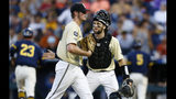 Vanderbilt pitcher Jake Eder, left, is greeted by Philip Clarke during the eighth inning of Game 3 of the NCAA College World Series baseball finals against Michigan in Omaha, Neb., Wednesday, June 26, 2019. (AP Photo/John Peterson)