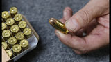 In this photo taken Tuesday, June 11, 2019, Chris Puehse, owner of Foothill Ammo displays a .45 caliber bullet for sell at his store in Shingle Springs, Calif. Californians will have to undergo criminal background checks every time they buy ammunition starting July 1 under a 2016 voter-approved ballot initiative. (AP Photo/Rich Pedroncelli)