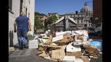 Un hombre pasa junto a una pila de basura con la cúpula de la basílica de San Pedro del Vaticano al fondo, en Roma, el 24 de junio de 2019. (AP Foto/Andrew Medichini)