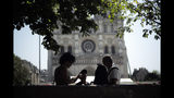 Tourists chat under a tree in front of Notre Dame Cathedral, Wednesday, June 26, 2019 in Paris. High temperatures are expected to go up to 39 degrees Celsius (102 Fahrenheit) in the Paris area later this week and bake much of the country, from the Pyrenees in the southwest to the German border in the northeast. (AP Photo/Kamil Zihnioglu)