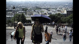 Tourists climb the steps leading to the Sacre Coeur basilica Wednesday, June 26, 2019 in the Montmartre district of Paris. More than half of France is on alert for high temperatures and the hot weather is expected to last until the end of the week. (AP Photo/Kamil Zihnioglu)
