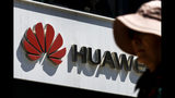 FILE - In this May 29, 2019, file photo, a woman walks by a Huawei retail store in Beijing. A federal jury in Texas rejected Wednesday, June 26, 2019, claims by Chinese telecom-equipment maker Huawei Technologies that Silicon Valley start-up CNEX stole its trade secrets. (AP Photo/Andy Wong, File)
