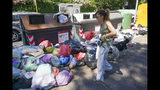 In this photo taken on Monday, June 24, 2019, a woman walks by uncollected garbage, in Rome. Doctors in Rome are warning of possible health hazards caused by overflowing trash bins in the city streets, as the Italian capital struggles with a renewed garbage emergency aggravated by the summer heat.(AP Photo/Andrew Medichini)