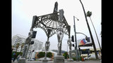 """Pedestrians walk past the """"Four Ladies of Hollywood"""" gazebo on Hollywood Boulevard in Los Angeles, on Wednesday June 19, 2019. Officials say someone climbed the more than two-story tall public art piece and stole a statue of Marilyn Monroe. Los Angeles Councilman Mitch O'Farrell says a witness saw someone climb the gazebo on the Hollywood Walk Fame and sawed off the statue. (AP Photo/Richard Vogel)"""