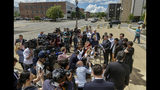 Members of the media crowd around the family of slain University of Illinois scholar Yingying Zhang to hear an address from attorney Wang Zhidong after a jury found Brendt Christensen guilty of her murder, Monday, June 24, 2019, in Peoria, Ill. (Matt Dayhoff/Journal Star via AP)