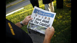 "FILE - In this June 29, 2018, file photo, Steve Schuh, county executive of Anne Arundel County, holds a copy of the Capital Gazette near the scene of a shooting at the newspaper's office in Annapolis, Md. At a time when journalists are being branded ""the enemy of the people,"" staff members at the Capital Gazette newspaper are feeling renewed appreciation in their community, a year after a gunman went on a newsroom rampage that left five of their colleagues dead. (AP Photo/Patrick Semansky, File)"
