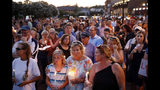 "FILE - In this June 29, 2018, file photo, mourners stand in silence during a vigil in response to a shooting at the Capital Gazette newsroom, in Annapolis, Md. At a time when journalists are being branded ""the enemy of the people,"" staff members at the Capital Gazette newspaper are feeling renewed appreciation in their community, a year after a gunman went on a newsroom rampage that left five of their colleagues dead. (AP Photo/Patrick Semansky, File)"