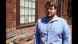 In this June 12, 2019, photo, Chase Cook, a Capital Gazette journalist, stands in downtown Annapolis, Md. Cook says while it has been a difficult year grappling with lingering effects of a last year's newsroom shooting that left five colleagues dead, reporters at the newspaper have a renewed passion for local journalism after receiving widespread support from the community. (AP Photo/Brian Witte)