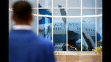 A member of Diplomatic Security stands guard on the tarmac as the plane for Secretary of State Mike Pompeo is reflected in a glass building, in preparation for Pompeo's departure from Abu Dhabi, United Arab Emirates, Tuesday, June 25, 2019, from where he will head to an undisclosed location. (AP Photo/Jacquelyn Martin, Pool)