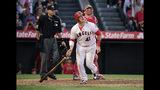 El jugador de los Angelinos de Los Ángeles, Justin Bour, observa su jonrón de tres carreras, cerca del receptor de los Rojos de Cincinnati, Curt Casali, y el umpire del plato, Pat Hoberg, durante el octavo inning de un juego de béisbol, el miércoles 26 de junio de 2019, en Anaheim, California. (AP Foto/Mark J. Terrill)