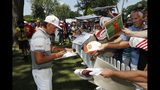 Rickie Fowler signs autographs during the Pro-Am for the Rocket Mortgage Classic golf tournament, Wednesday, June 26, 2019, in Detroit. (AP Photo/Carlos Osorio)