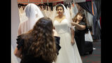 In this Friday, June 21, 2019, photo Ann Campeau,, right, owner of Strut Bridal, fits a new dress on inventory manager Stefanie Zuniga at her shop in Tempe, Ariz. Cut-rate prices on websites that sell wedding dresses direct from China put pressure on Campeau, who owns four bridal shops in California and Arizona. She has had customers come in after seeing low-end gowns online and expecting to get a dress at a similar price. (AP Photo/Matt York)