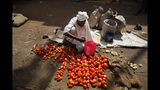 A Sudanese street vendor cleans his tomatoes to sell them, in Khartoum, Sudan, Wednesday, June 26, 2019. A leading Sudanese opposition figure says the African Union and Ethiopia have joined forces in renewed efforts to mediate the crisis in Sudan and bring the ruling generals and protest leaders back to the negotiating table. (AP Photo/Hussein Malla)