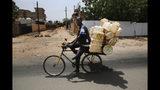 A Sudanese rides his bike, in Khartoum, Sudan, Wednesday, June 26, 2019. (AP Photo/Hussein Malla)