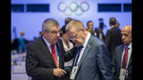 International Olympic Committee, IOC, President Thomas Bach from Germany, left, speaks with Australian IOC member John Coates, right, during the 134th Session of the International Olympic Committee (IOC), at the SwissTech Convention Centre, in Lausanne, Switzerland, Tuesday, June 25, 2019. (Jean-Christophe Bott/Keystone via AP)